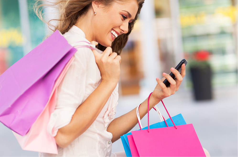 Woman carrying shopping bags and a cell phone