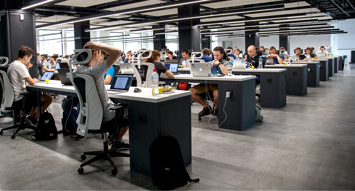 modern office with a lot of people working on laptops