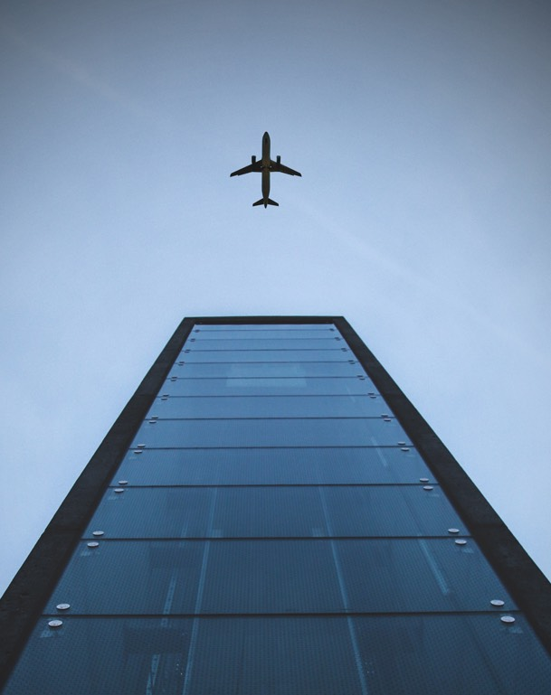airplane taking off above a high building
