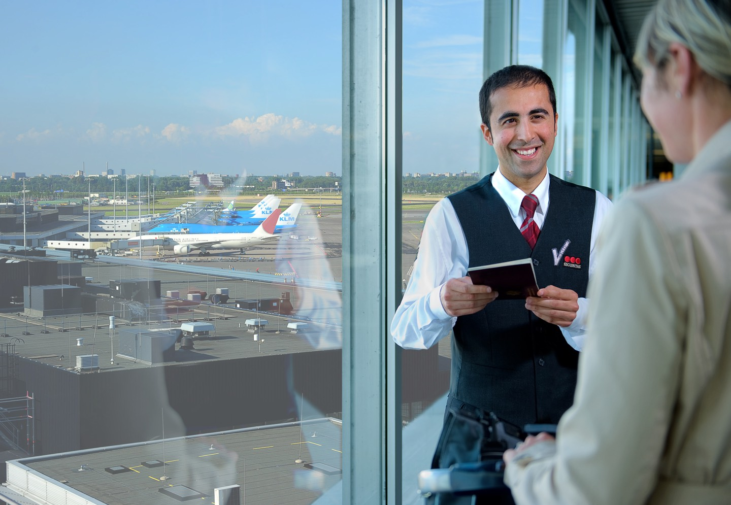 Securitas security officer talking to a customer at an airport